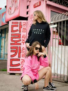 black and pink zipper hoodie with white komera neza print logo