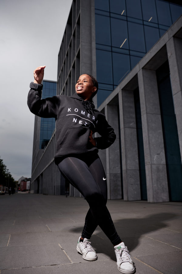 black woman wearing black hoodie with white komera neza print logo