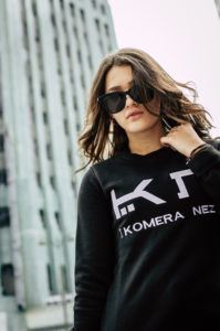 woman wearing a womens black sweatshirt with white komera neza logo