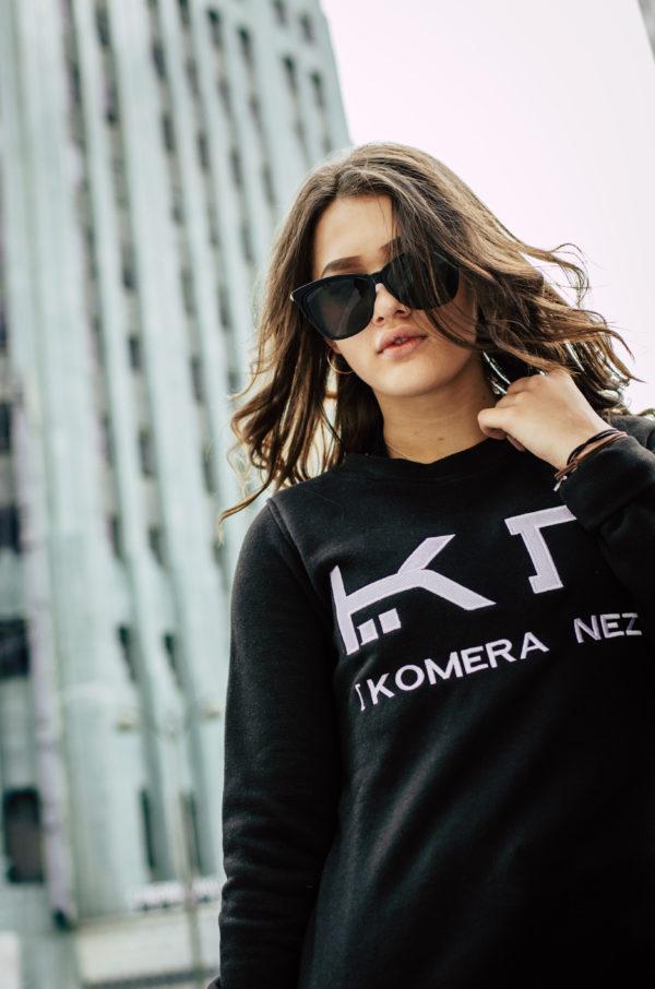 woman wearing a womens black sweatshirt with white komera neza logo