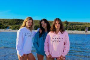 womens white, blue, and pink hoodie with black komera neza print logo