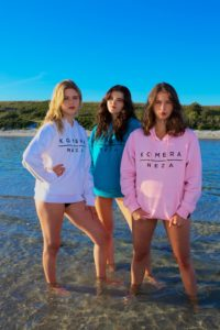 womens white, blue, and pink hoodie with black komera neza print logo