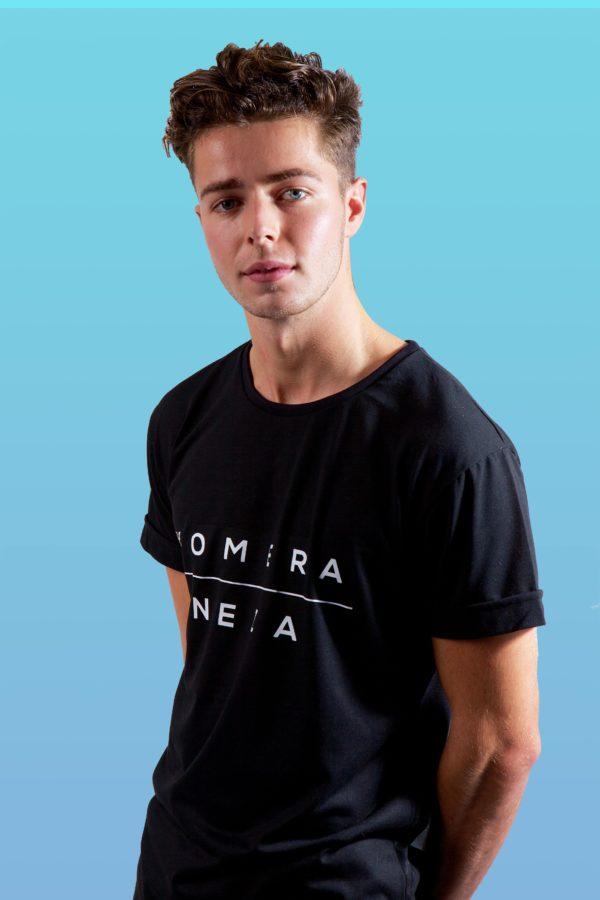 man wearing black t-shirt with white KOMERA NEZA print logo