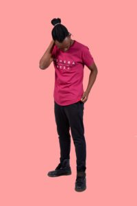 black male wearing burgundy t-shirt with white komera neza print logo