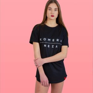 woman wearing a black t-shirt with white KOMERA NEZA print logo