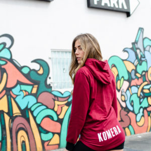 women wearing pocketless burgundy hoodie with white komera neza print logo