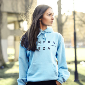 young woman wearing blue hoodie with black komera neza print logo
