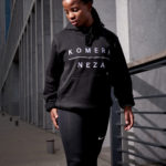 black girl wearing black hoodie with white KOMERA NEZA print logo