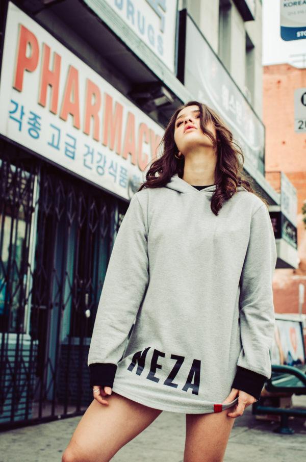 woman wearing pocketless grey hoodie with black komera neza print logo