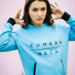 woman wearing neon blue zipper hoodie with black komera neza print logo