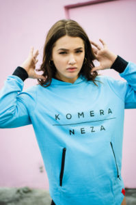 woman wearing neon blue zipper hoodie with black komera neza print logo