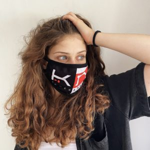 woman wearing a black face mask with KOMERA NEZA logo